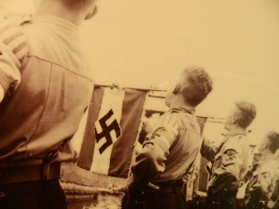 A member of the Hitler Youth holds a Nazi flag